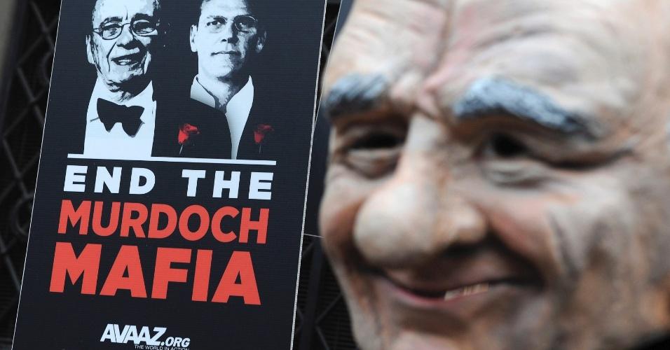 Manifestante mostra cartaz com imagens de James e Rupert Murdoch, proprietário do império midiático News Corporation, em frente a corte em Londres que investiga os padrões éticos da imprensa inglesa e as relações entre jornalistas e políticos