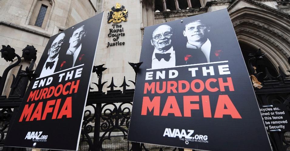 Manifestantes mostram cartazes com imagens de James e Rupert Murdoch, proprietário do império midiático News Corporation, em frente a corte em Londres que investiga os padrões éticos da imprensa inglesa e as relações entre jornalistas e políticos