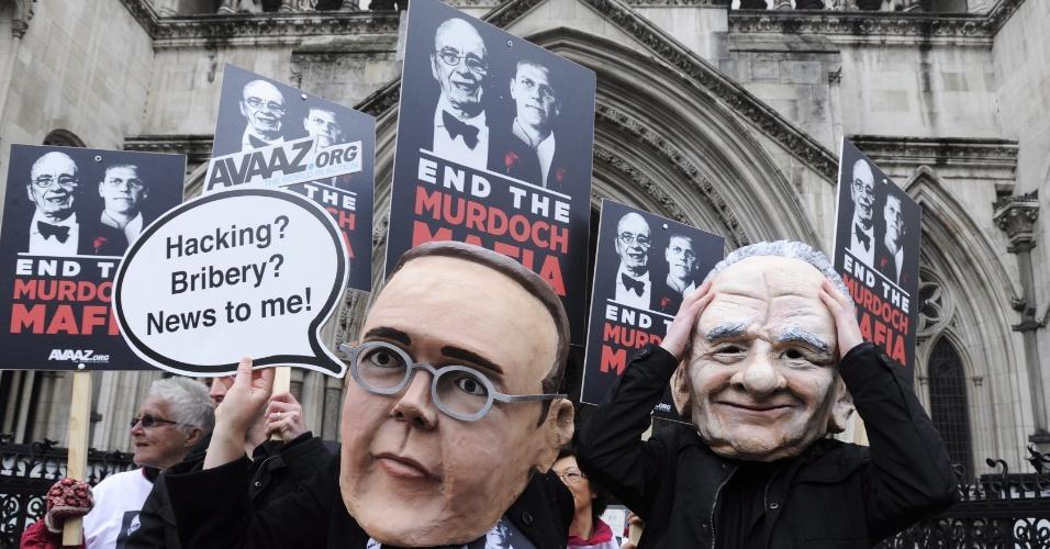 Manifestantes usam máscaras de James e Rupert Murdoch, proprietário do império midiático News Corporation, em frente a corte em Londres