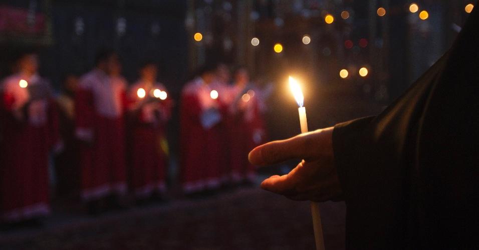Membro do clero armênio com uma vela durante oração especial pelo aniversário do assassinato em massa de armênios no Império Otomano em 1915, em Jerusalém