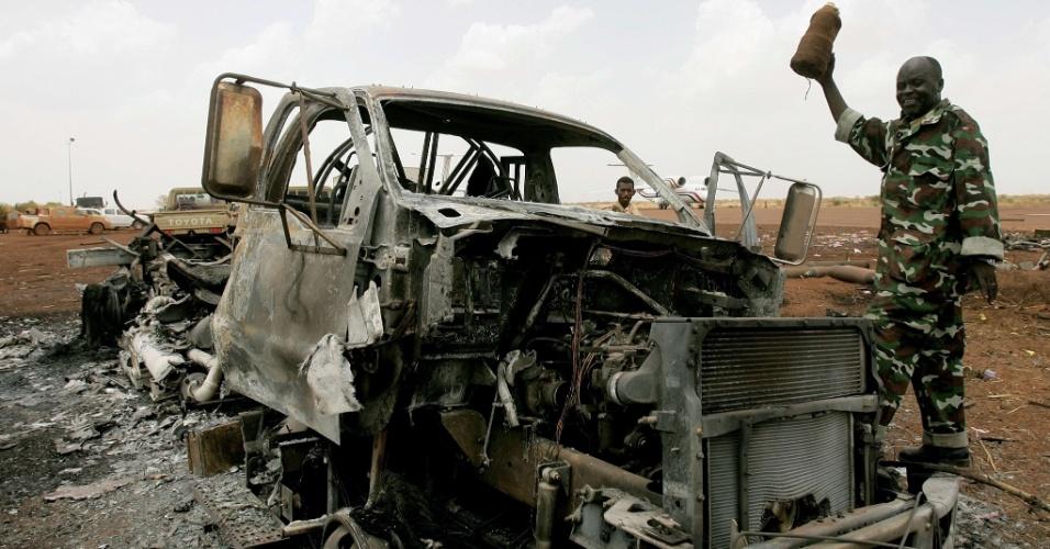 Militar sudanês caminha próximo a veículo queimado no aeroporto de Heglig, região petrolífera disputada com Sudão do Sul