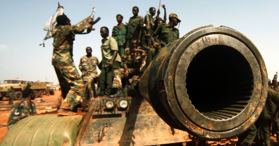 Soldados do Sudão sobem em tanque do Sudão do Sul durante visita do presidente sudanês, Omar al-Bashir, à região petrolífera de Heglig