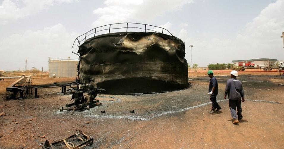 Trabalhadores sudaneses observem estrutura destruída na região petrolífera de Heglig
