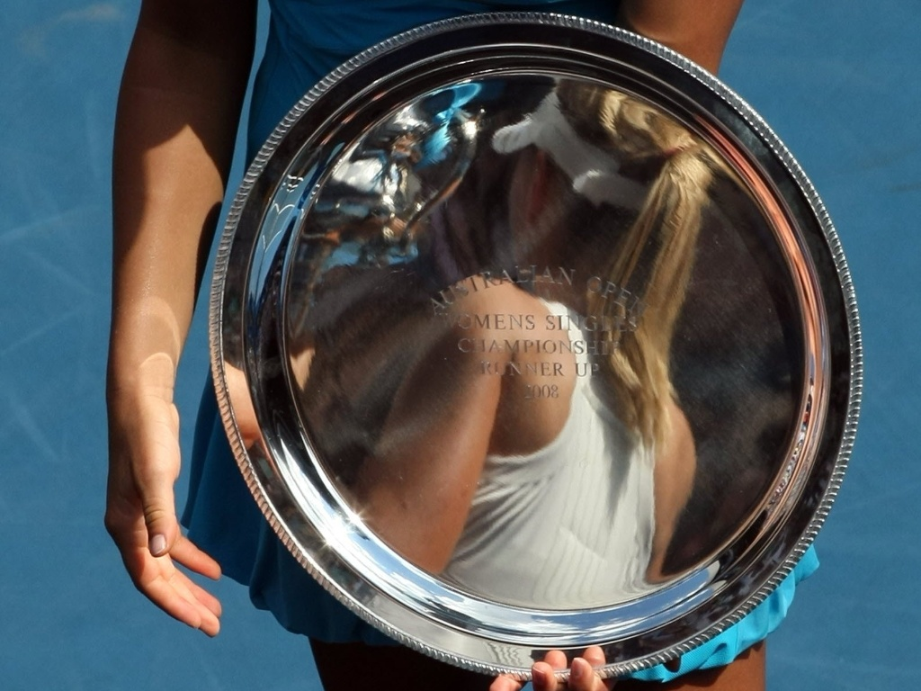 Ana Ivanovic segura troféu de vice-campeã do Aberto da Austrália com reflexo da campã, Sharapova