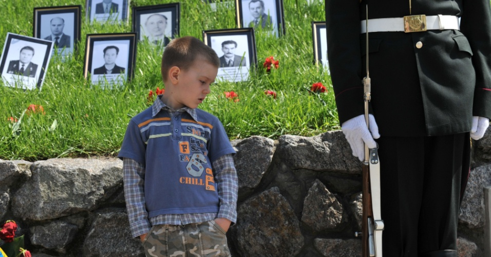 Garoto olha para o rifle de um soldado em guarda no memorial, em Kiev, na Ucrânia, dedicado às vítimas da tragédia de Tchernobil