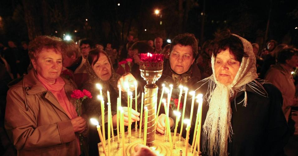 Mulheres acendem velas em memorial às vítimas de Tchernobil, em Kiev, na Ucrânia