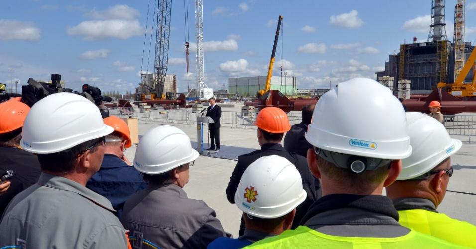 Operários escutam o presidente da Ucrânia, Viktor Yanukovych (centro), em frente às obras de construção de uma nova redoma de contenção de radiação em Tchernobil