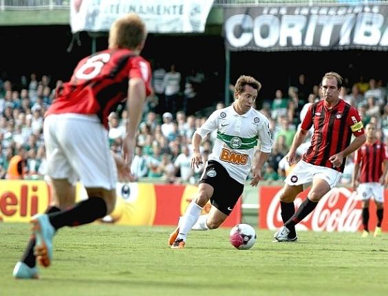 Everton Ribeiro conduz a bola, marcado por Paulo Baier, do Atlético, no Atle-Tiba (22/04/2012)
