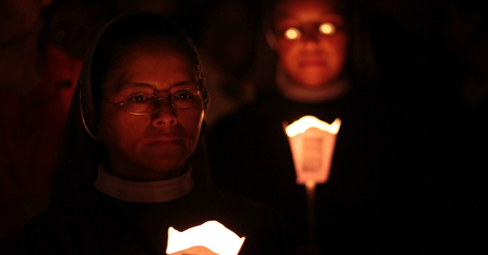 Freiras seguram velas do lado de fora da Igreja San Sebastián, na Cidade da Guatemala, em cerimônia que lembra o 14º aniversário de Don Juan José Gerardi, assassinado após publicar depoimentos de vítimas de conflito interno armado na Guatemala em 1998