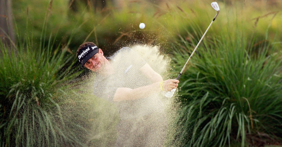 Golfista Keegan Bradley bate para fora de um buraco de areia no torneio Zurich Classic, no TPC Louisiana, em Avondale