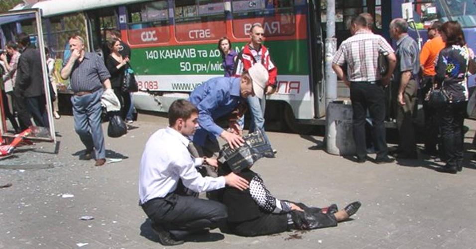 Homem ajuda vítima de explosão a se levantar na cidade de Dnipropetrovsk (Ucrânia). Nesta sexta-feira (27), a cidade foi atingida por três explosões, que deixaram pelo menos 15 pessoas feridas, segundo autoridades