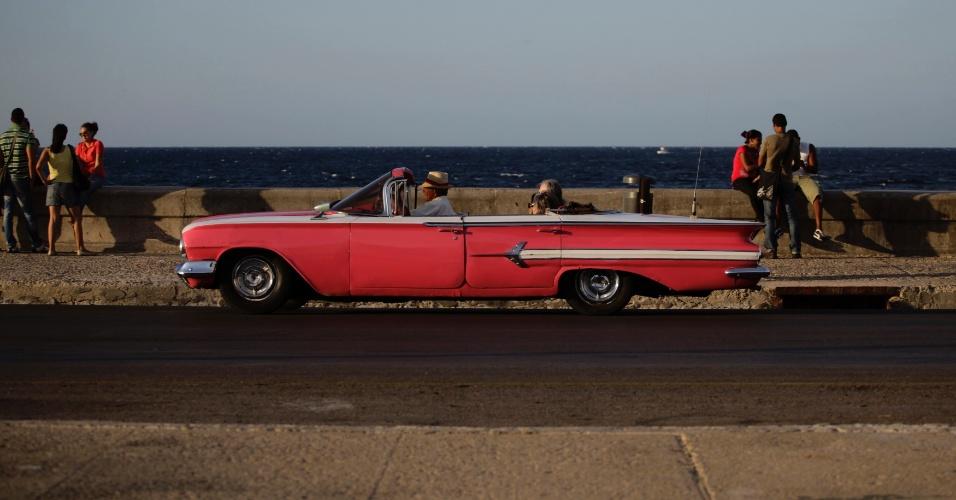 Turistas passam de carro por El Malecón, com o mar de Havana, em Cuba, ao fundo