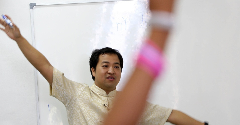 O professor Xu Lu faz gestuais e performances em sala de aula para explicar as  diferenças de sons na língua chinesa. Os alunos se divertem, imitam e respondem em coro com o professor