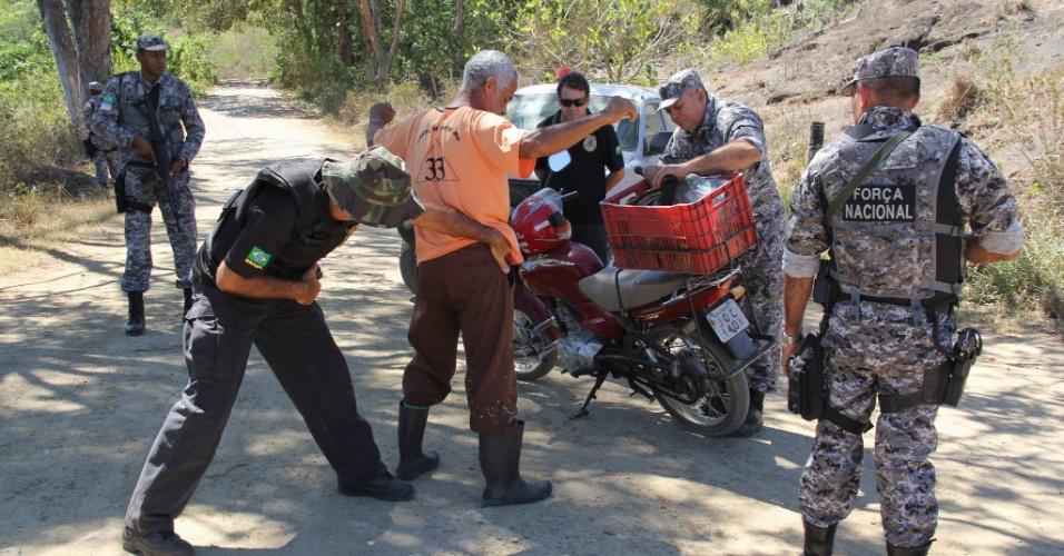Agentes da Força Nacional e da Polícia Federal revistam motociclistas que passam por áreas de conflito em Pau Brasil (BA). O clima de tensão começou desde que índios pataxós ocuparam 68 fazendas na região