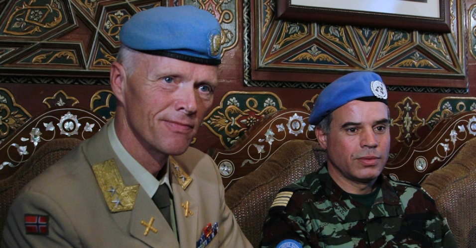 Chefe da missão de supervisão das Nações Unidas na Síria, o general norueguês Robert Mood (de farda clara), chega a Damasco. No fundo da sala onde ele foi recebido por autoridades, uma foto do presidente sírio Bashar al-Assad