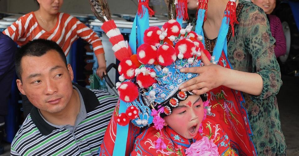Foto da sexta-feira (27), mostra um pai chinês que prepara a filha, sonolenta, para uma apresentação na cidade de Zhengyangguan, em que ela representará uma divindade