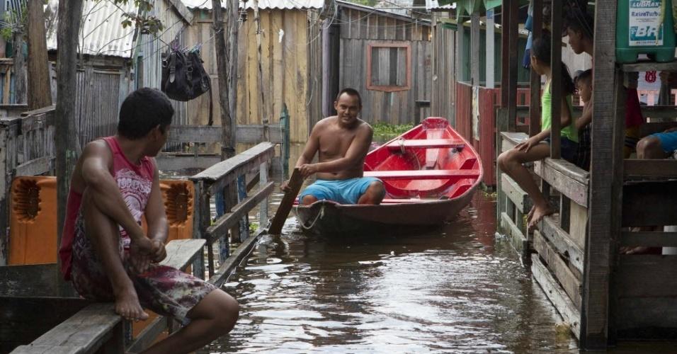 Homem anda de canoa após enchente do rio Negro, no bairro da Glória, em Manaus (AM). A capital amazonense declarou estado de emergência por causa dos alagamentos, que atingem mais de 3.600 famílias, de acordo com a Defesa Civil