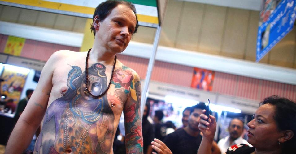 Homem faz tatuagem durante a Convenção Internacional de Tatuagem, no Nepal