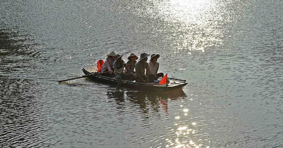 Mulher rema barco levando turistas na província de Ninh Binh, no Vietnã