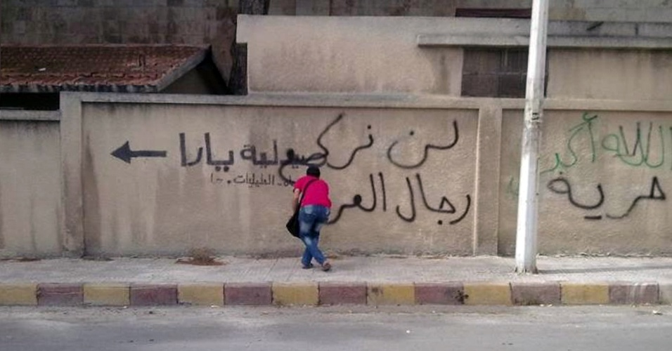 Homem picha frases anti-regime em muro na cidade de Hama, na S&#237;ria, nesta segunda-feira (30)