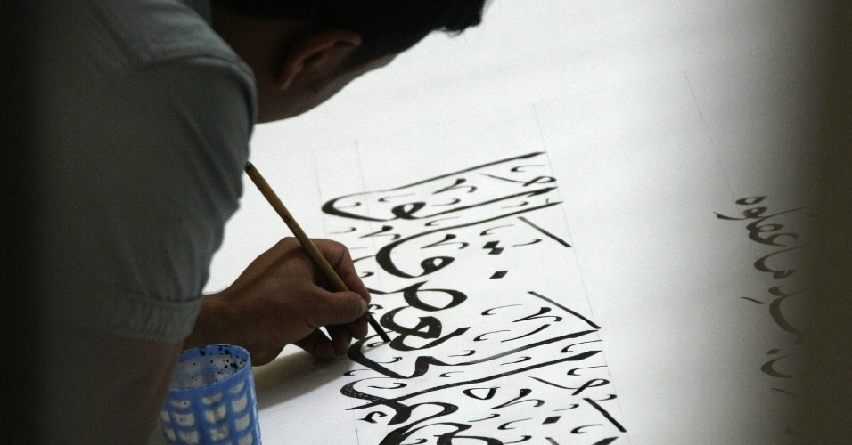 O calígrafo iraquiano Hussein al-Kharsan escreve versos do Alcorão na tentativa de bater o recorde do Guinness Book de maior versão do livro sagrado já escrita à mão