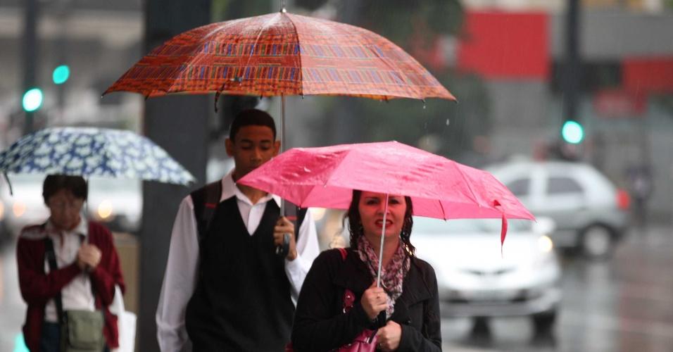 Pessoas se protegem da chuva e do frio na manhã desta segunda-feira (30) na avenida Paulista, na região central da capital paulista