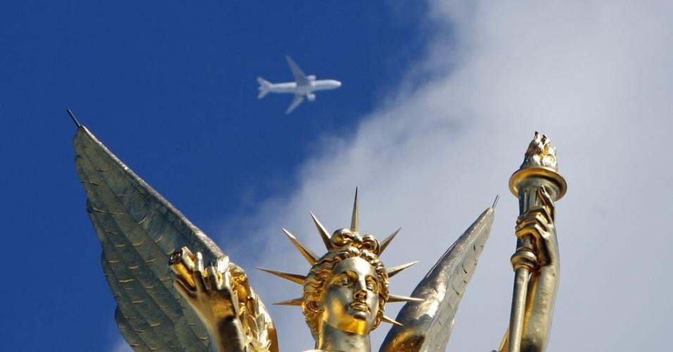 Avião passa no céu sobre a escultura que faz parte do teatro Opera, de Paris (França)