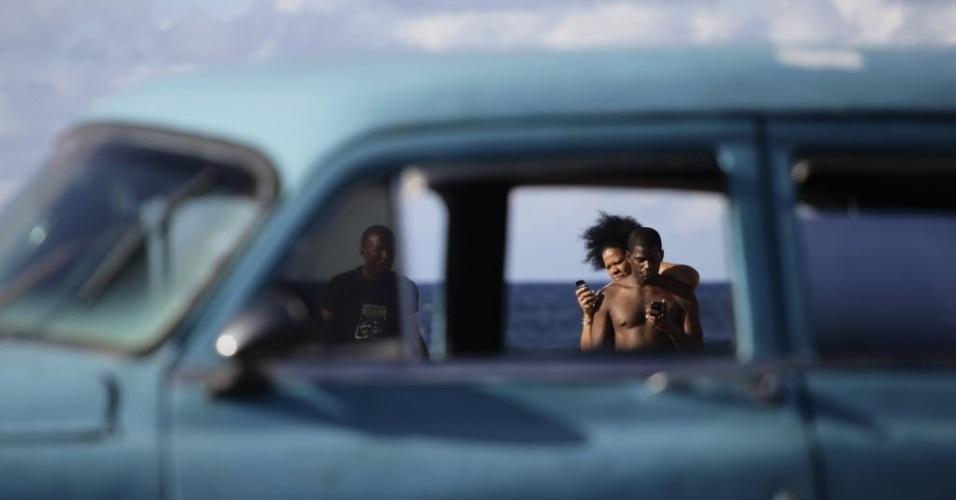 Casal namora no Malecón, o calçadão à beira-mar em Havana, capital de Cuba
