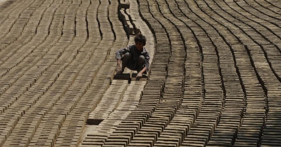 Garoto faz tijolos em olaria da cidade de Lahore, no Paquistão