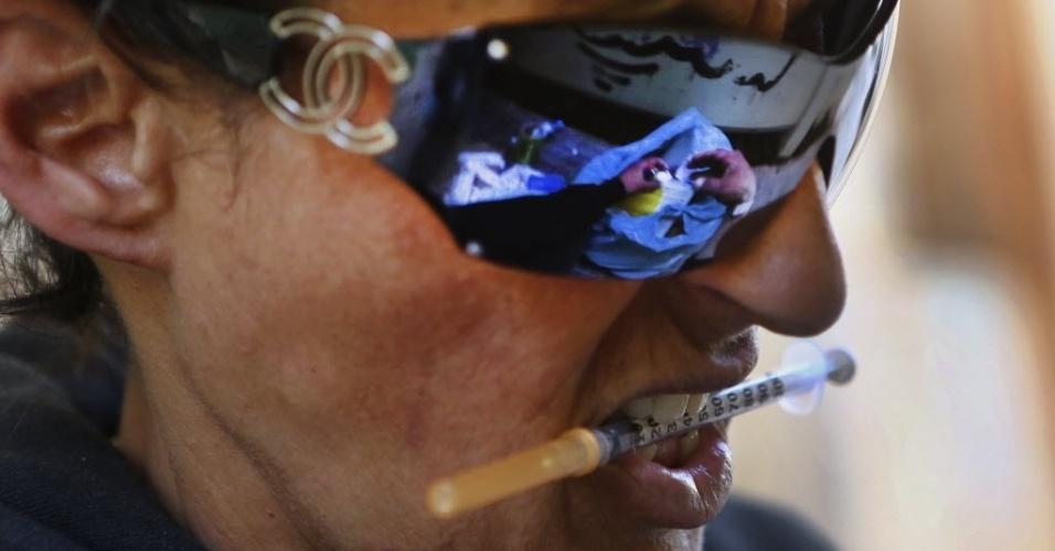 Viciado em speedball, mistura cocaína e heroina, prepara uma dose da droga no centro de Atenas (Grécia)