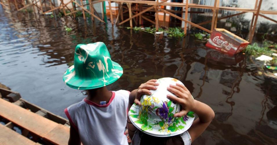2.mai.2012 - Crianças andam por uma plataforma improvisada em uma das ruas inundadas pelas águas do Rio Negro, um dos dois principais afluentes do rio Amazonas, em Manaus