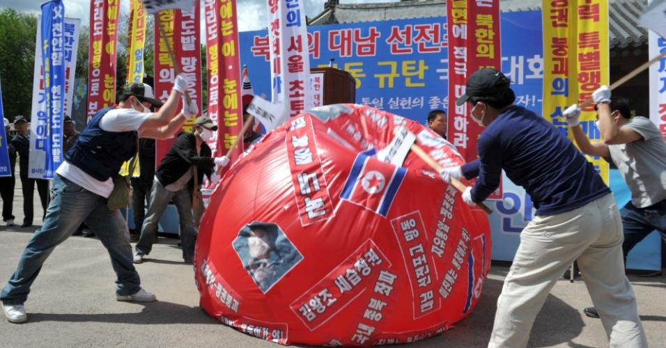 Homens usando máscaras usam machados para destruir um balão com imagens do líder da Coreia do Norte, Kim Jong-Un, durante protesto de ativistas conservadores em Seul, na Coreia do Sul