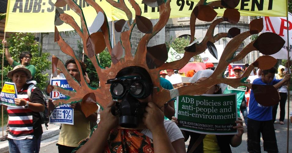 Manifestante usa fantasia de árvore com máscara de gás para simbolizar a destruição do meio ambiente em protesto durante a 45ª Reunião Anual do Conselho do Banco Asiático de Desenvolvimento em Manila, nas Filipinas
