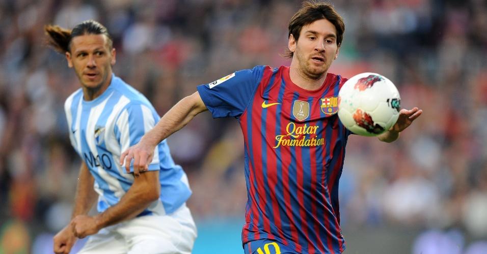 O argentino Lionel Messi, do Barcelona, passa por seu compatriota Demichelis, do Málaga