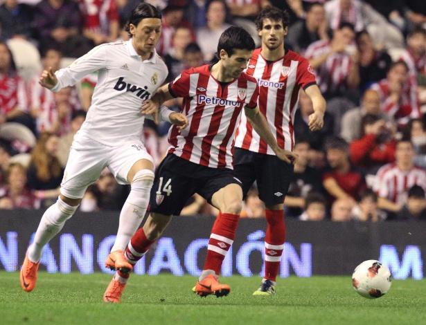 O jogador do Athletic Bilbao Susaeta (centro) disputa a bola com o alemão Özil, do Real Madrid