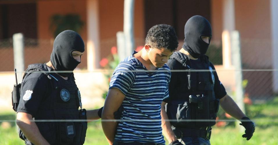 3.mai.2012 - Aparecido Souza Alves, 22, um dos executores confessos da chacina de Doverlândia (GO), é conduzido por agentes da Polícia Civil até o local do crime para participar de reconstituição do crime