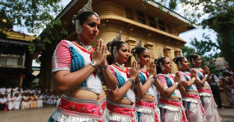 3.mai.2012 - Dançarinas rezam antes de se apresentar em templo de Colombo, no Sri Lanka