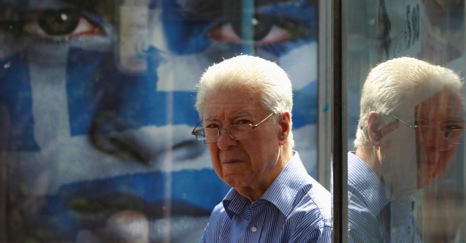 Homem espera por ônibus em Atenas, na Grécia, ao lado de cartaz da campanha eleitoral. O país terá eleições no domingo, dia 6