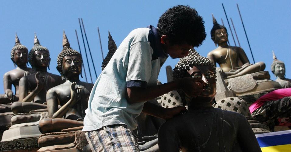 3.mai.2012 - Homem limpa estátua de Buda no templo budista Gangaramaya em Colombo, no Sri Lanka, nesta quinta-feira (3). No dia 5 de maio, os cingaleses realizam o festival Vesak Day Poya, para comemorar o nascimento e a iluminação de Buda