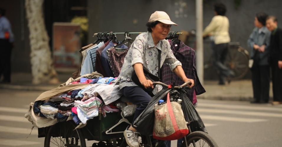 3.mai.2012 - Mulher vende roupas nas ruas de Xangai, na China, nesta quinta-feira (3), a bordo de uma bicicleta