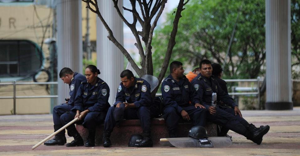 3.mai.2012 - Policiais descansam em banco durante protesto de mais de 1,6 mil estagiários de medicina e 300 enfermeiros para exigir subsídios educacionais e aumentos salariais do governo, em Tegucigalpa, capital de Honduras. A greve forçou o governo a declarar estado de emergência nacional para o sistema público de saúde, com soldados e bombeiros atendendo pacientes em hospitais