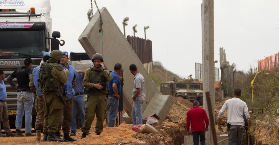 Soldados israelenses e da ONU trabalham na construção de um muro na fronteira de Israel com o Líbano, na cidade de Metula