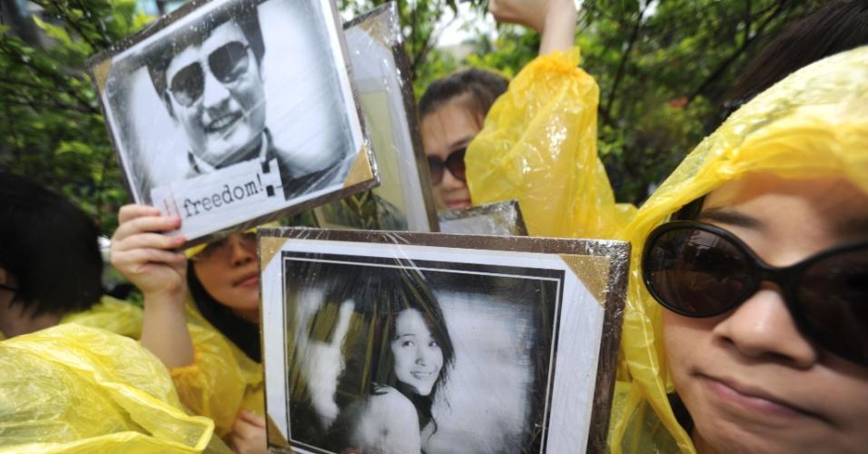 4.mai.2012 - Ativistas de direitos humanos mostram cartazes do dissidente chinês cego Chen Guangcheng (esquerda) e seu apoiador He Peirong em protesto do lado de fora de instituto norte-americano em Taipei (Taiwan)