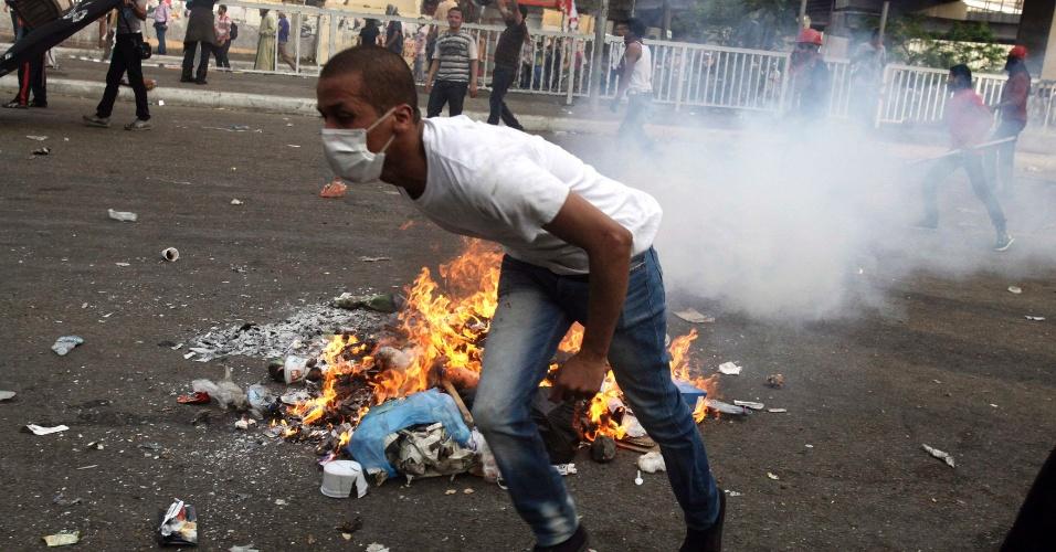 4.mai.2012 - Manifestante tenta fugir de gás lacrimogêneo lançado pelas forças de segurança do Egito durante protesto realizado no Cairo contra candidatos das eleições presidenciais e o chefe do Exército, o marechal Hussein Tantawi