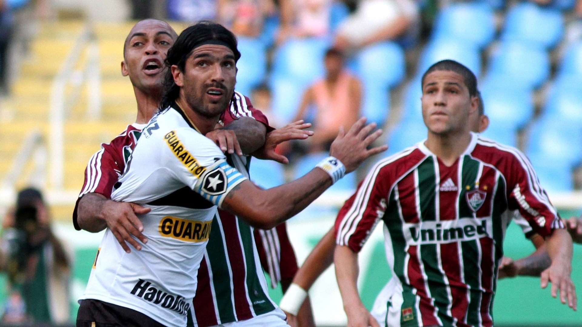 O atacante Loco Abreu, do Botafogo, e o zagueiro Leandro Euzbio, do Fluminense, disputam espao na rea