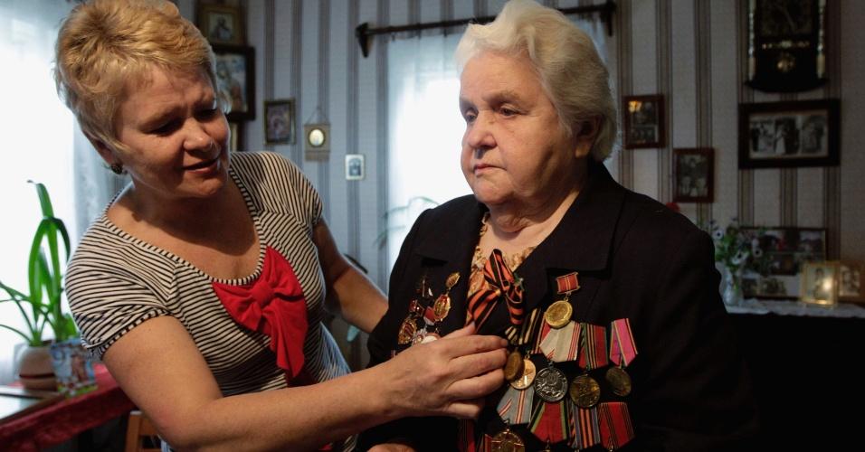 8.mai.2012 - A veterana da 2ª Guerra Mundial Anna Beliai (dir.), 86, enfeita sua roupa com as condecorações recebidas com ajuda da filha, na cidade de Turov, em Belarus