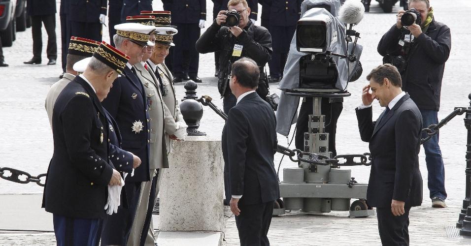 8.mai.2012 - O atual presidente francês, Nicolas Sarkozy (dir.) e o seu sucessor, François Holland (esq.), participam de cerimônia em homenagem ao 67° aniversário da vitória dos Aliados sobre o Nazismo alemão, no Arco do Triunfo, em Paris