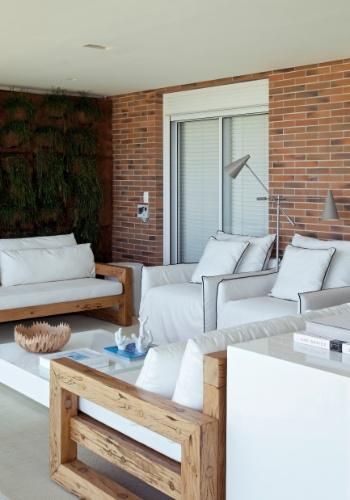 Descontração com toques de requinte dão a atmosfera da varanda que tem mesa de centro em nanoglass, desenhada pelo arquiteto Diego Revollo e executada pela M.S.A.. Em uma das paredes, um jardim vertical com cactos-macarrão e irrigação automatizada