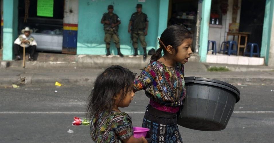11.mai.2012 - Duas meninas andam perto de um grupo de soldados do Exército que patrulham El Limon, na Guatemala