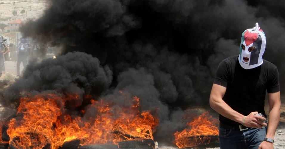 11.mai.2012 - Manifestante palestino passa por pneus queimados durante conflito contra soldados israelenses na vila de Kafr Qaddum, na Palestina